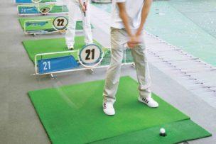 ゴルフ練習場で練習する初心者